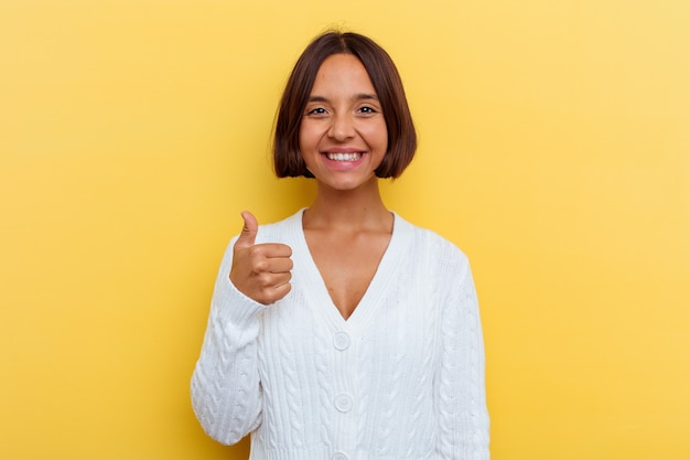 Young mixed race woman isolated on yellow background smiling and raising thumb up