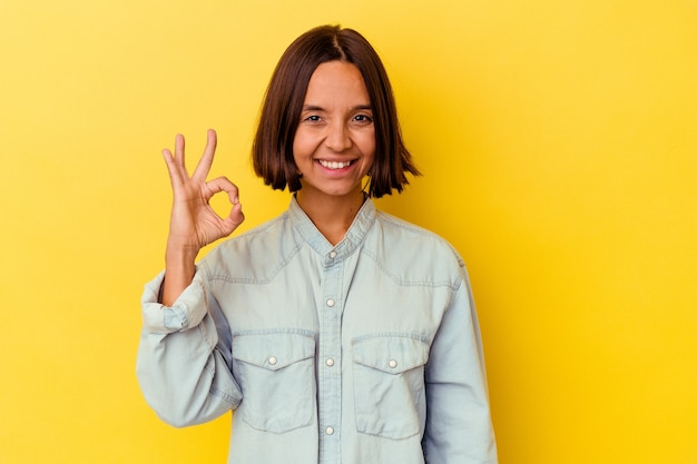 Young mixed race woman isolated on yellow background winks an eye and holds an okay gesture with hand.