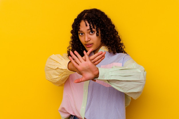 Young mixed race woman isolated on yellow doing a denial gesture
