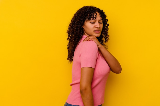 Young mixed race woman isolated on yellow having a shoulder pain.