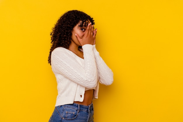 Young mixed race woman isolated on yellow wall blink through fingers frightened and nervous.