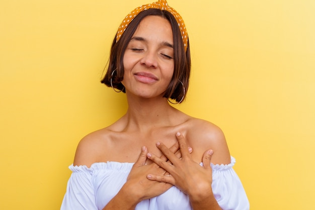 Young mixed race woman isolated on yellow wall laughing keeping hands on heart, concept of happiness.