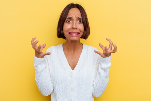 Young mixed race woman isolated on yellow wall screaming with rage.