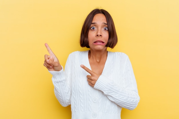 Young mixed race woman isolated on yellow wall shocked pointing with index fingers to a copy space.