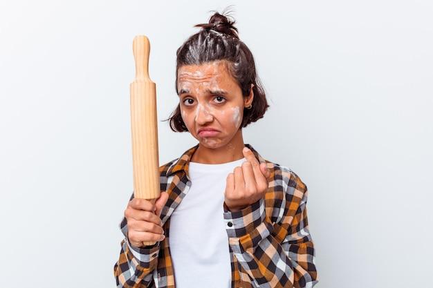 젊은 혼합 된 인종 여자 초대 가까이 와서 당신 손가락으로 가리키는 흰 벽에 고립 된 빵을 만들기.