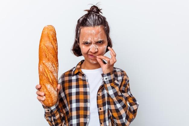 비밀을 유지하는 입술에 손가락으로 흰 벽에 고립 된 빵을 만드는 젊은 혼합 된 인종 여자.