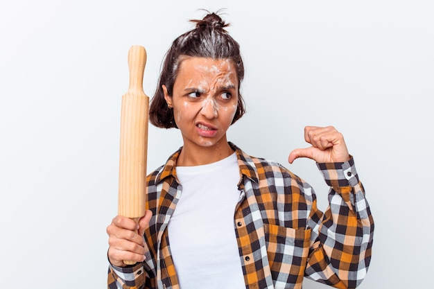Young mixed race woman making bread isolated on white wall feels proud and self confident, example to follow.