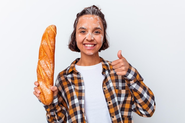 Young mixed race woman making bread isolated on white wall smiling and raising thumb up