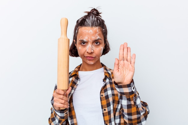Young mixed race woman making bread isolated on white wall standing with outstretched hand showing stop sign, preventing you.