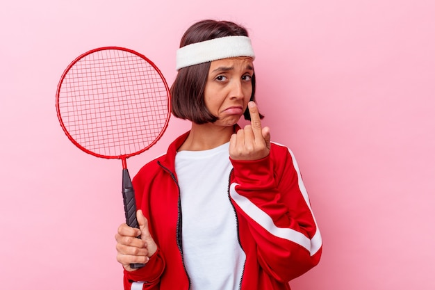 젊은 혼합 된 경주 여자 초대 가까이 와서 당신 손가락으로 가리키는 분홍색 배경에 고립 배드민턴을 재생합니다.