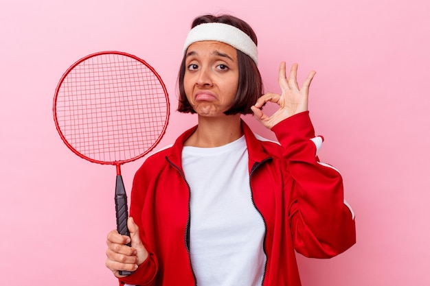 ピンクの壁に隔離されたバドミントンをしている若い混血の女性は陽気で自信を持って大丈夫なジェスチャーを示しています。