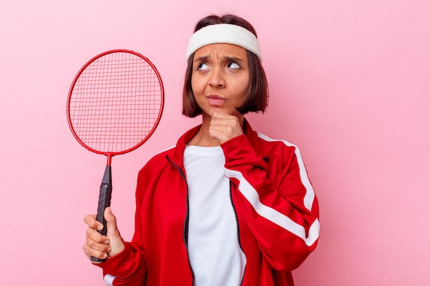 젊은 혼혈 여자 배드민턴을 의심스럽고 회의적인 표정으로 옆으로보고 분홍색 벽에 고립.