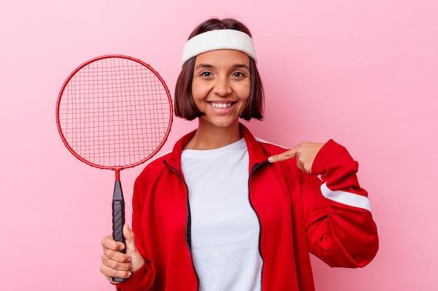 자부심과 자신감, 셔츠 복사 공간을 손으로 가리키는 분홍색 벽 사람에 고립 된 배드민턴을 재생하는 젊은 혼혈 여자