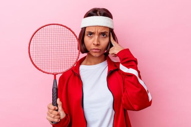 젊은 혼합 된 경주 여자 배드민턴 손가락으로 사원을 가리키는 분홍색 벽에 고립 생각, 작업에 초점을 맞춘.