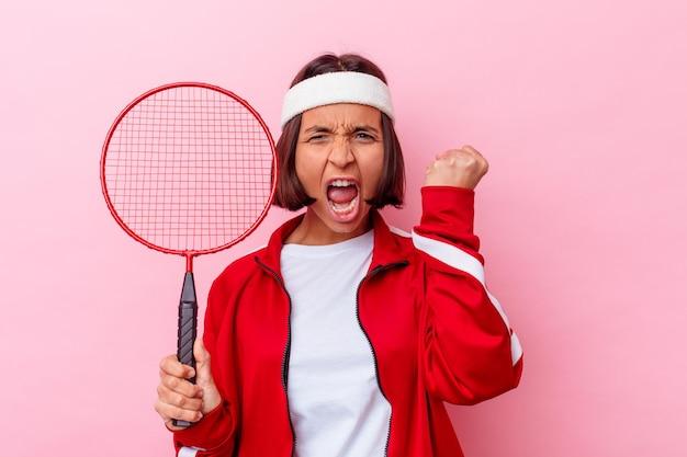 勝利、勝者のコンセプトの後に拳を上げるピンクの壁に分離されたバドミントンを演奏する若い混血の女性。