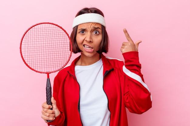 집게 손가락으로 실망 제스처를 보여주는 분홍색 벽에 고립 된 배드민턴 젊은 혼합 된 인종 여자.