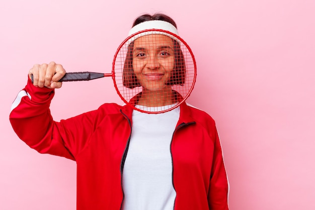 분홍색 벽에 고립 된 배드민턴 젊은 혼혈 여자