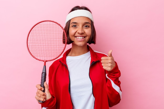 Young mixed race woman playing badminton isolated on pink wall smiling and raising thumb up