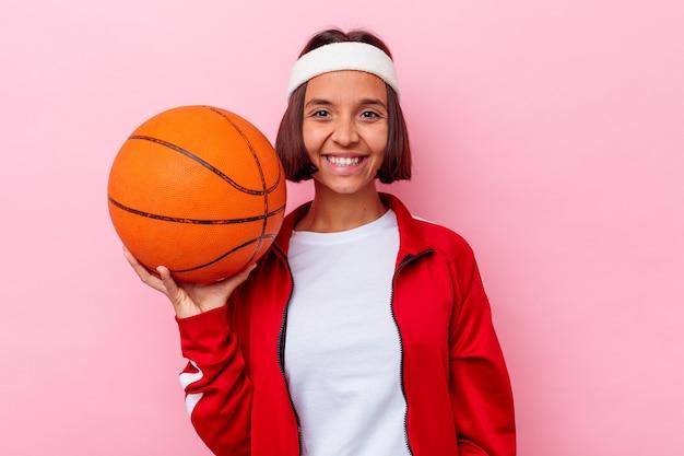 ピンクの背景に分離されたバスケットボールをしている若い混血の女性は幸せ、笑顔、陽気な。