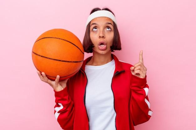 ピンクの背景に分離されたバスケットボールをしている若い混血の女性は、口を開けて逆さまを指しています。