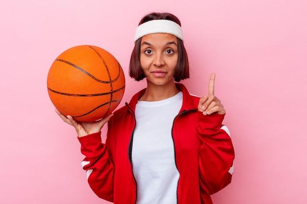 ピンクの背景に分離されたバスケットボールをしている若い混血の女性は、指でナンバーワンを示しています。