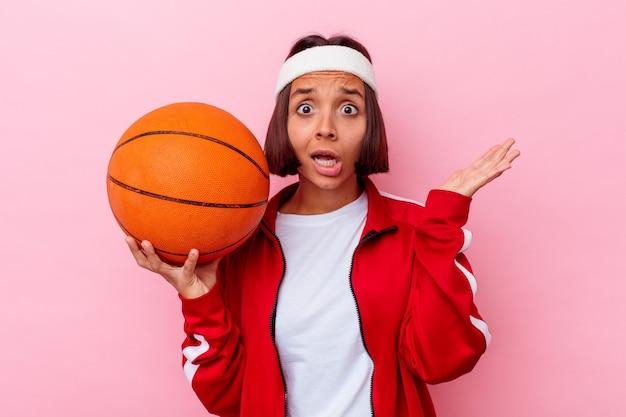 ピンクの背景に分離されたバスケットボールをしている若い混血の女性は驚いてショックを受けました。