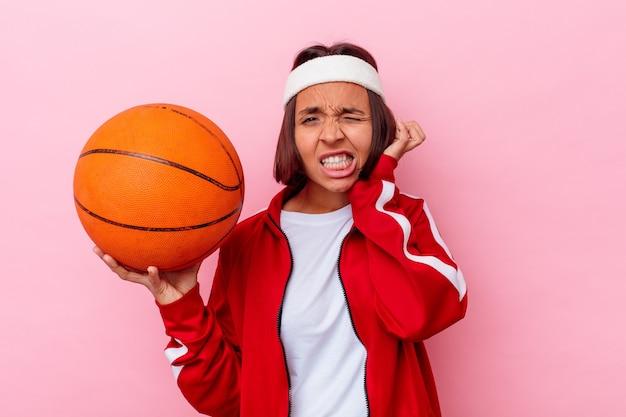 手で耳を覆うピンクの壁に分離されたバスケットボールをしている若い混血の女性。