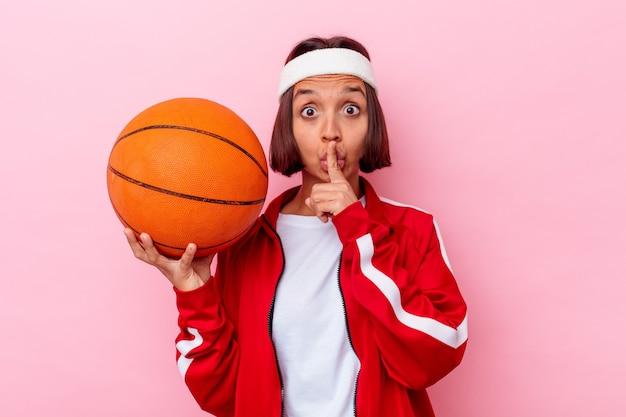 비밀을 유지하거나 침묵을 요구하는 분홍색 벽에 고립 된 농구를하는 젊은 혼합 된 인종 여자.