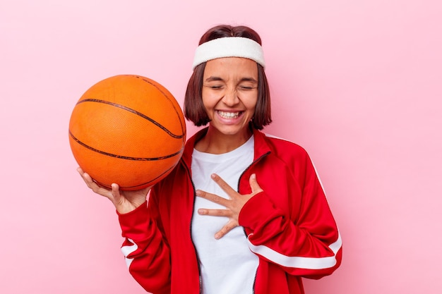 분홍색 벽에 고립 된 농구를하는 젊은 혼합 된 경주 여자 큰 소리로 가슴에 손을 유지 웃음.