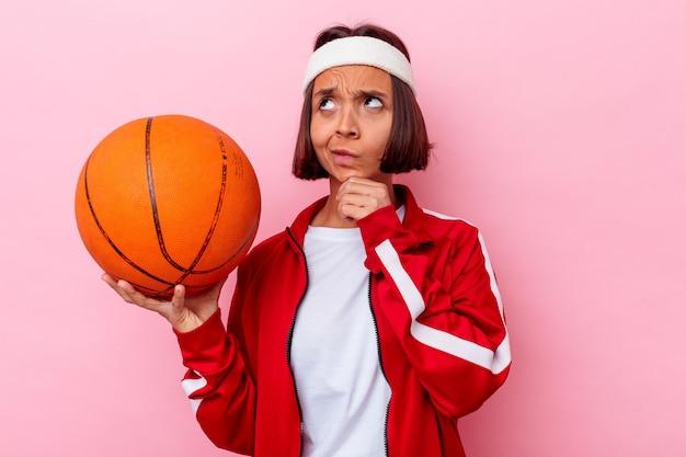 疑わしいと懐疑的な表情で横向きにピンクの壁に分離されたバスケットボールをしている若い混血の女性。