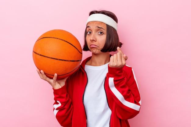 젊은 혼합 된 경주 여자 초대 가까이와 서 당신 손가락으로 가리키는 분홍색 벽에 고립 된 농구.