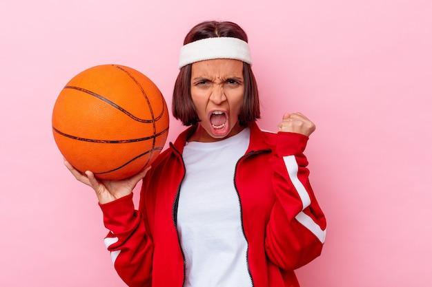 勝利、勝者の概念の後に拳を上げるピンクの壁に分離されたバスケットボールをしている若い混血の女性。