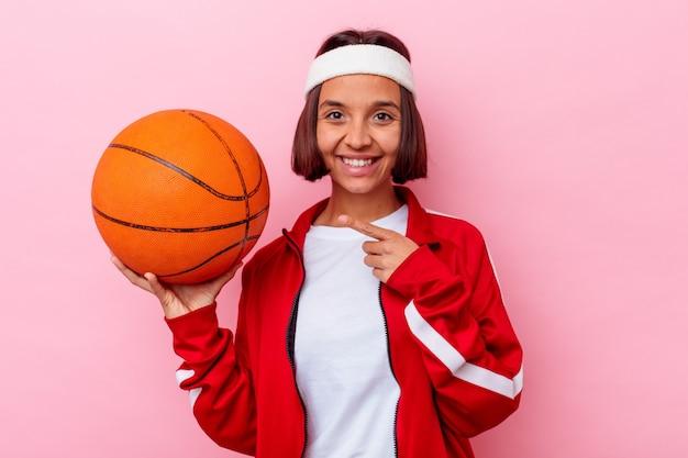 ピンクの壁に孤立したバスケットボールをしている若い混血の女性が笑顔で脇を指して、空白のスペースで何かを示しています。