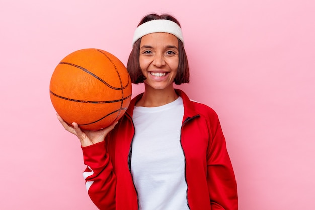 Young mixed race woman playing basketball isolated on pink background happy, smiling and cheerful.