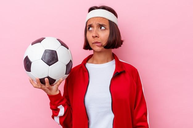 Молодая женщина смешанной расы, играющая в футбол на розовом фоне, смущена, чувствует себя сомнительной и неуверенной.