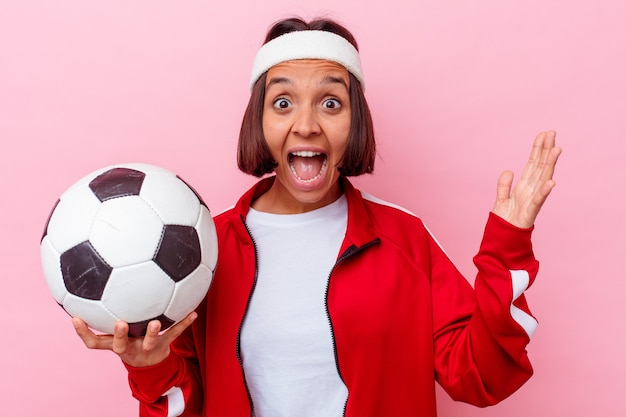 ピンクの背景に分離されたサッカーをしている若い混血の女性は、嬉しい驚きを受け取り、興奮し、手を上げます。