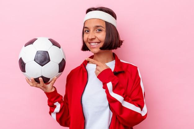 Молодая женщина смешанной расы играет в футбол, изолированные на розовом фоне, улыбаясь и указывая в сторону, показывая что-то на пустом месте.