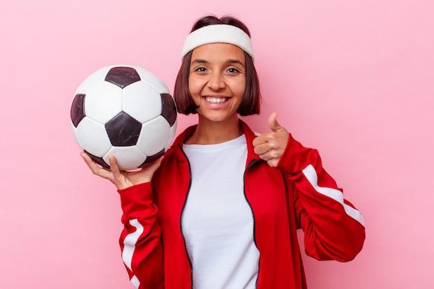 Молодая женщина смешанной расы играет в футбол на розовом фоне, улыбаясь и поднимая палец вверх