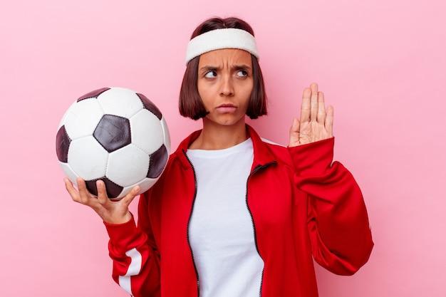 Молодая женщина смешанной расы играет в футбол, изолированные на розовом фоне, стоя с протянутой рукой, показывая знак остановки, предотвращая вас.