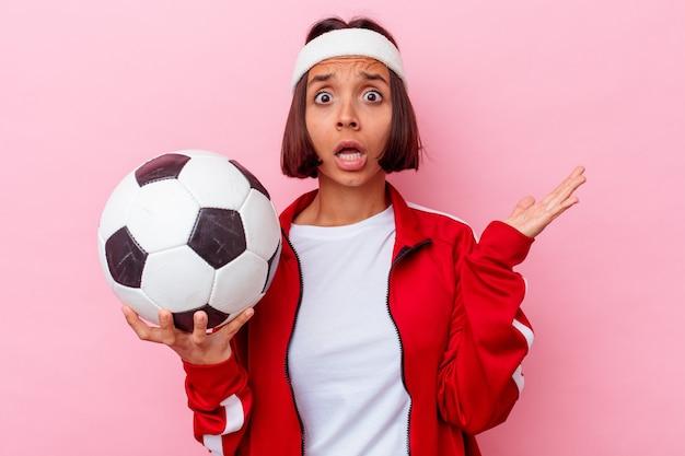 Молодая женщина смешанной расы, играющая в футбол на розовом фоне удивлена и шокирована.