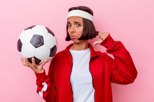 Молодая женщина смешанной расы, играющая в футбол, изолированная на розовой стене, чувствует гордость и уверенность в себе, пример для подражания.
