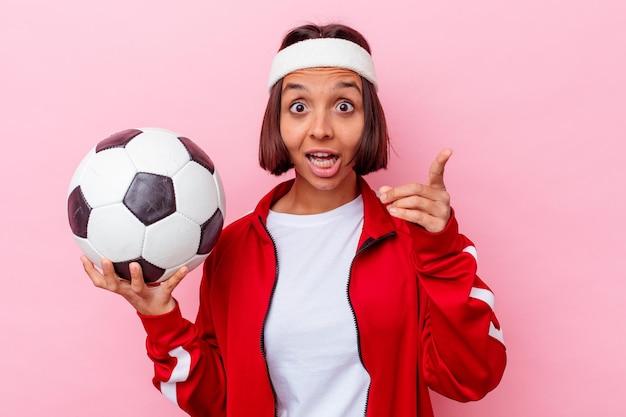 アイデア、インスピレーションのコンセプトを持つピンクの壁に分離されたサッカーをしている若い混血の女性。