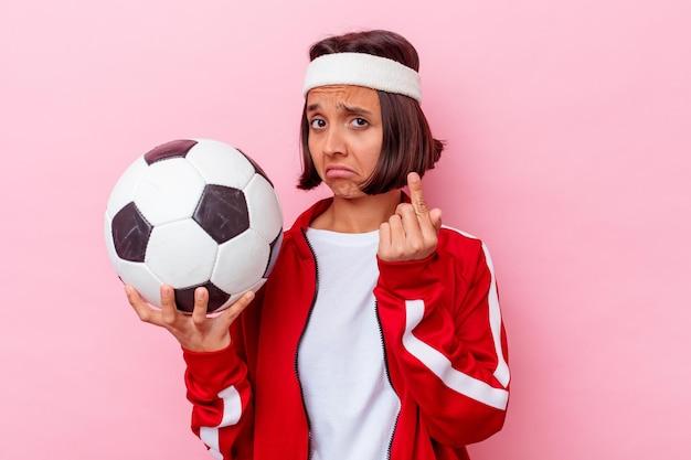 젊은 혼합 된 경주 여자 초대 가까이와 서 당신 손가락으로 가리키는 분홍색 벽에 고립 된 축구.