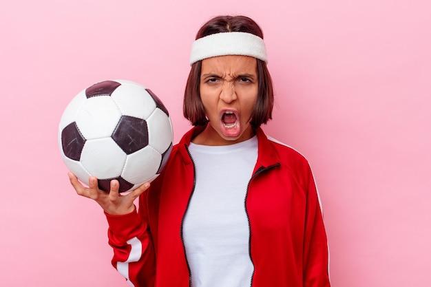 Молодая женщина смешанной расы, играющая в футбол, изолирована на розовой стене, кричала очень сердито и агрессивно.