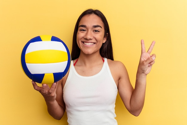 Young mixed race woman playing volleyball on the beach isolated on yellow background joyful and carefree showing a peace symbol with fingers.