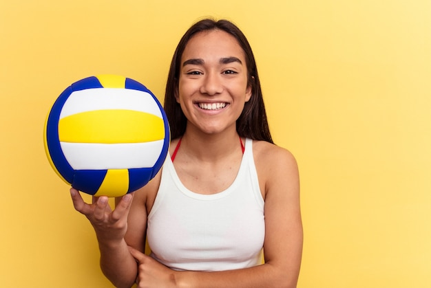 Young mixed race woman playing volleyball on the beach isolated on yellow background laughing and having fun.