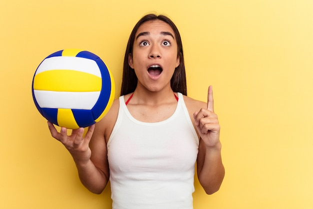 Young mixed race woman playing volleyball on the beach isolated on yellow background pointing upside with opened mouth.