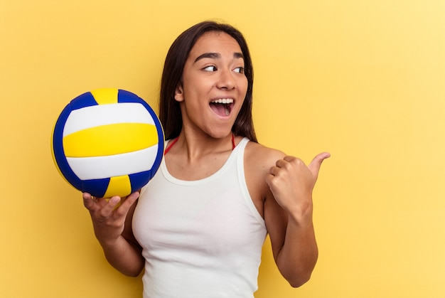 Young mixed race woman playing volleyball on the beach isolated on yellow background points with thumb finger away, laughing and carefree.