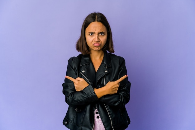 Young mixed race woman points sideways, is trying to choose between two options.