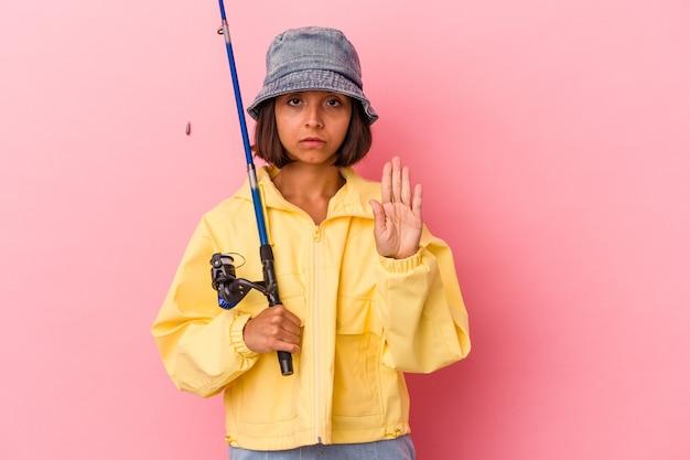 분홍색 배경에 격리된 채 낚시를 하는 젊은 혼혈 여성이 정지 신호를 보여주며 손을 뻗은 채 당신을 방해합니다.